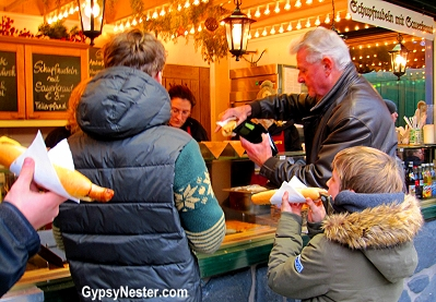 A family enjoys their half meter wursts at the Christmas Market in Passau, Germany
