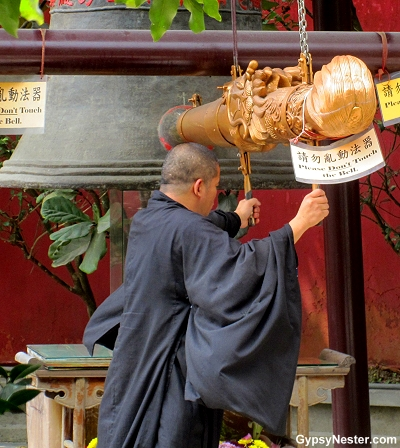 A monk rings a bell at the Big Buddha's monestary in Hong Kong, China
