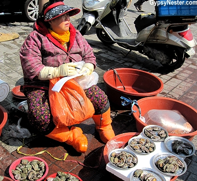 A woman sits outside the fish market in Busan, South Korea