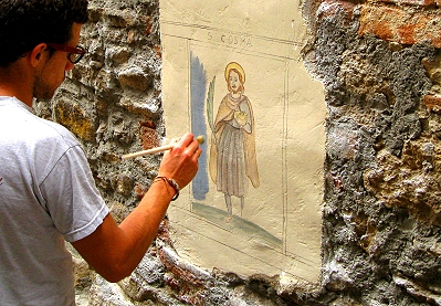 Artist painting frescoes directly on to the walls along the narrow streets of the old town