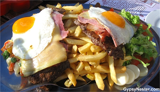 Chivito Gigante! Two huge hunks of cow, slices of ham, slabs of bacon, pounds of potatoes, and a veritable garden, all topped off with a couple fried eggs.
