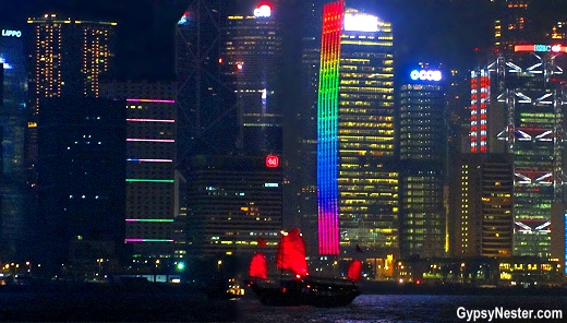 A traditional Chinese junk sets sail in Victoria Harbor amid Hong Kong's modern skyscrapers