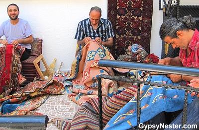 Men repairing Turkish rugs in a courtyard in Istanbul, Turkey