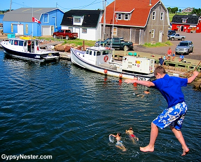 Kids jumping from a bridge into the Stanley River on Prince Edward Island