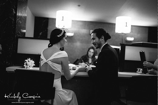 The bride and groom sit at a counter in NYC's city hall