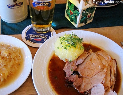 Ofenfrischer Schweinsbraten mit Kruste, dazu Knödel und Kraut, which translates exactly to: Oven Fresh pork roast with crust, with dumplings and sauerkraut in Passau, Germany