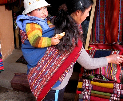 A baby has lunch in his mother's back in Peru