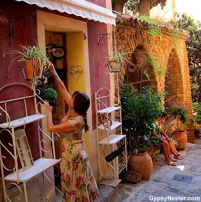 A shopkeeper opens her shop in Bormes-les-Mimosas, Provence, France