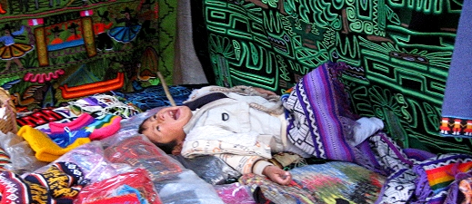 A child plays among her mother's wares in the Sacred Valley of Peru
