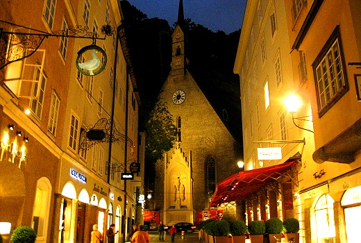 Charming Salzburg street with guild signs at night