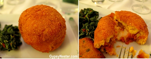 Arancino, a classic traditional Sicilian dish, arancino. Made with risotto filled with ragù, beef, and mozzarella, it's shaped into a ball, then deep-fried to a golden brown.