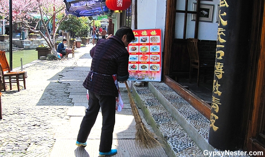 A woman sweeps in front of a shop in the water town of Zhujiajiao, China near Shanghai