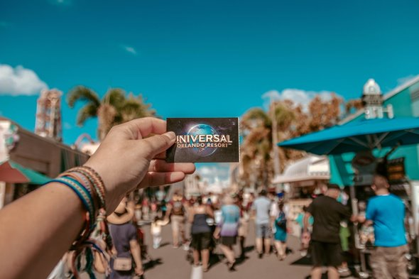 Figure 2: Famous for fun theme park, Orlando also belongs to the top cities for millennials in Florida for many other reasons. alt.tag: a person holding a ticked for the universal theme park