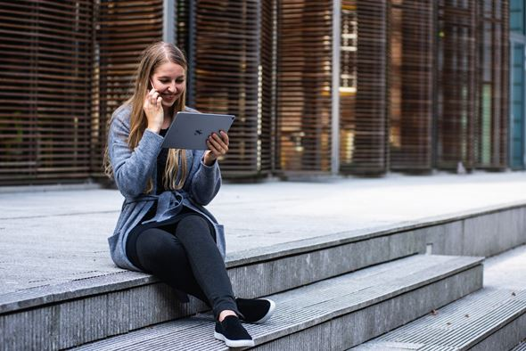 Figure 3: Organize your move and plan it in advance - you'll be in FLorida in no time! alt.tag: a millennial girl looking at a tablet and talking on the phone about the top cities for millennials in Florida
